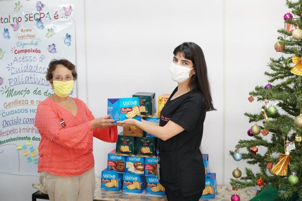 Psicóloga Flávia Nunes entrega o panetone para Júlia do Carmo, atendida pelo Serviço de Cuidados Paliativos do HB desde abril
